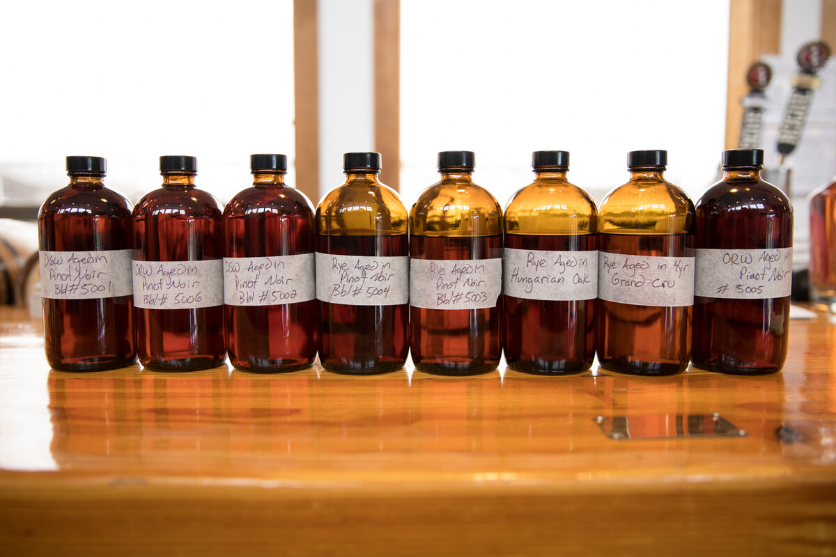 Sample bottles of the whiskeys that had been aged in used Pinot noir bottles lined up on the bar at Rogue Spirits Tasting Room in Newport, Oregon.